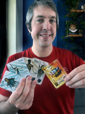 Wesley Cone with a hand of Empyrean HERO, the first card game he invented and developed. [Robert Thomason / Times-News]