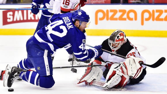 New Jersey Devils goalie Cory Schneider (35) makes a save on Toronto Maple Leafs center Tyler Bozak (42) during the second period of an NHL hockey game Thursday, Nov. 16, 2017, in Toronto. (Frank Gunn/The Canadian Press via AP)