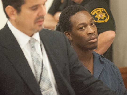 Najuquan Ross, right, looks on during a detention