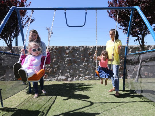 Alyssa Tavizon-Spinks, background left, and Jennifer Musshorn, background right, watch their daughters, Zoey and Ella, play on swings. The two mothers have been friends since they were children. Zoey is living with cystic fibrosis.