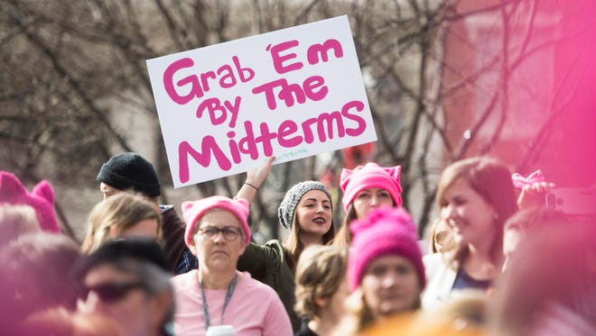 """A sign reading """"Grab 'em by the midterms"""" is held by an attendee at the  the Knoxville Women's March at Krutch park in downtown Knoxville Sunday, Jan. 21, 2017. The crowd grew to 14,000 and spanned 10 blocks."""