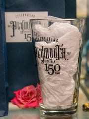 The museum store offers items celebrating Plymouth's 150th, including a pint glass.