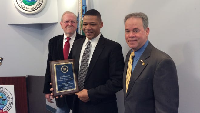 Spring Valley Police Officer Joseph Brown, a former U.S. Marine Corps sergeant, is the 2015 Buffalo Soldier Award recipient. Jerry Donnellan, director the Veterans Service Agency of Rockland, left, and Rockland County Executive Ed Day, right, congratulated Brown, center, at the ceremony.