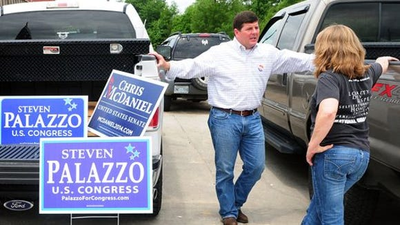 In this 2014 file photo, U.S. Rep Steven Palazzo speaks with Tina Sims of Hattiesburg in the parking lot of Mak's in Eastabuchie during the Republican Party primary election.