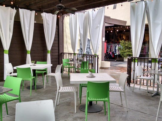 The green and white outdoor patio is a comfortably cozy option for diners who enjoy their meals alfresco.