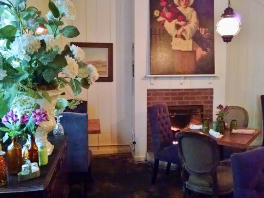 One of two interior dining rooms, this one features a fireplace, a painting, flowers and multiple tables with high-back purple chairs.