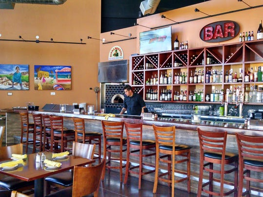 The extensive bar area includes a bar made of reclaimed wood, flat-screen TVs and artwork.
