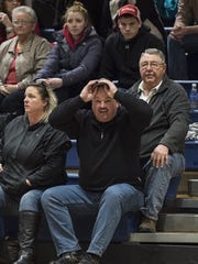 Howard Mellott, father of McConnellsburg's Bronwyne Mellott, sitting with his wife Karla, adjusts his cap during last year's District 5 championship game. McConnellsburg claimed the 2017 District 5 Class 2A title over the weekend, 30 years after he won a district championship as a basketball player for Forbes Road. Karla was also a district champion at Forbes Road.