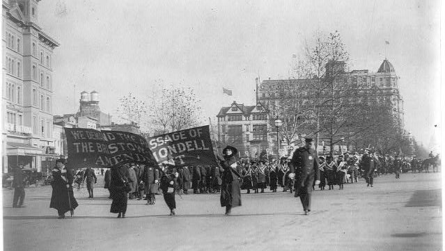 """Photograph from 1917 shows four women marching ahead of large procession with the banner """"We demand the passage of the Bristow-Mondell amendment"""" at the woman suffrage parade in Washington, D.C."""