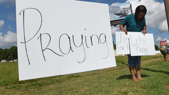 Nikki Sanders posts signs of prayer along Barksdale Blvd before a prayer service for law enforcement at City of Truth Worship Center in Bossier City.