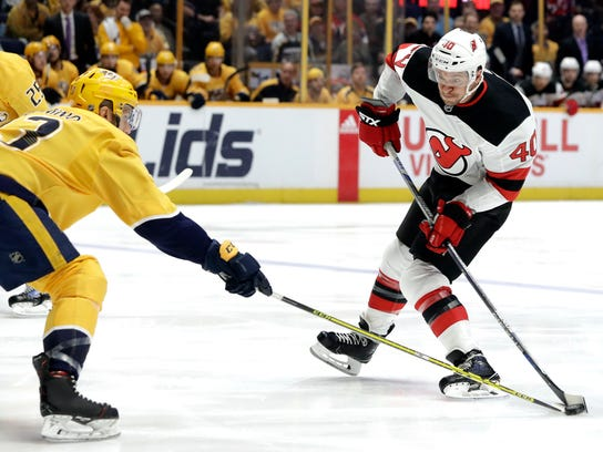Nashville Predators defenseman Nick Bonino (13) blocks a shot by New Jersey Devils right wing Michael Grabner (40), of Austria, in the first period of an NHL hockey game Saturday, March 10, 2018, in Nashville, Tenn. (AP Photo/Mark Humphrey)