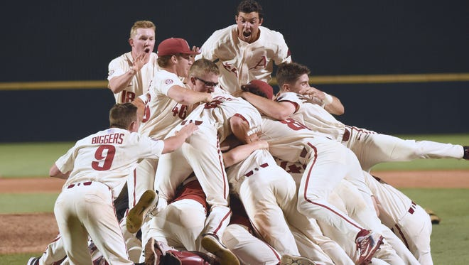 Arkansas Razorback players celebrate after defeating South Carolina on Monday night to advance to the College World Series.