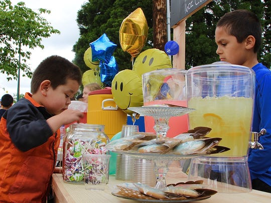 Emanuel Rodriguez,4, left, digs into a bowl of candy at Christopher Gonzalez's lemonade stand at the  Keizer Iris Festival as part of Lemonade Day on Saturday, May 20, 2017.
