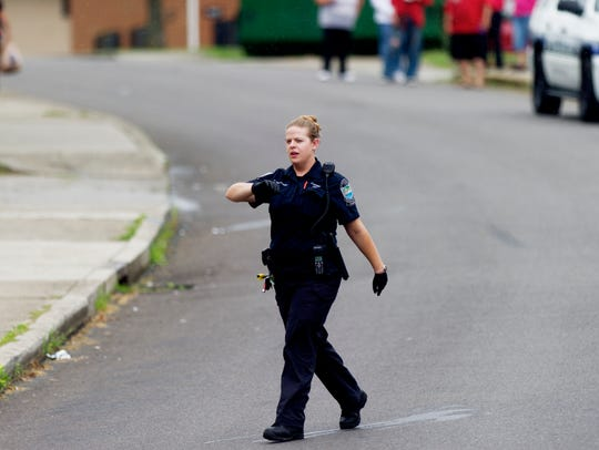 A police officer clears the area at the scene of a