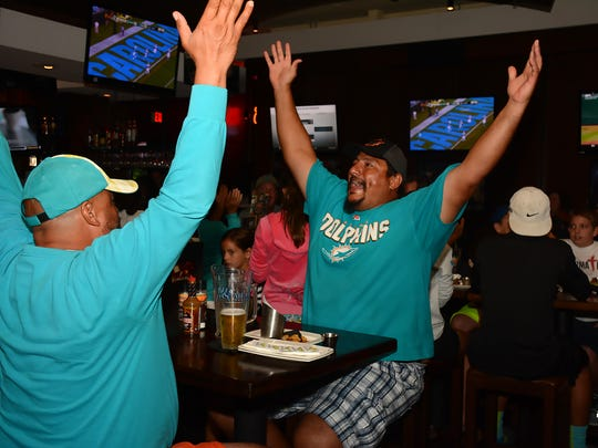 Brothers Will, left, and David Kline celebrate a Miami Dolphins touchdown Saturday night at Bokamper's. Lance Shearer/Special to the Daily News