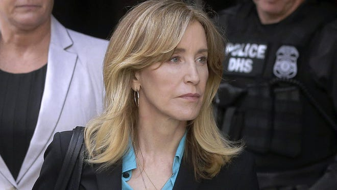 In this April 3, 2019 file photo, actress Felicity Huffman arrives at federal court in Boston to face charges in a nationwide college admissions bribery scandal. In a court filing on Monday, April 8, 2019, Huffman agreed to plead guilty in the cheating scam.