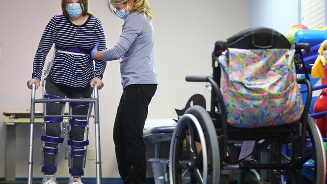 With assistance from physical therapist Renee Parsons, Isabel Kirby walks across the physical therapy room last week at Akron Children's Hospital's Medina campus.