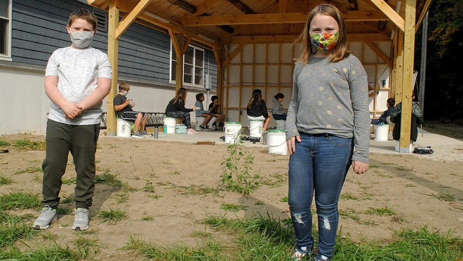 Fourth-graders Owen Graves of Eliot and Cassidy Thompson of South Berwick stand outside the pavilion built behind Great Works School in South Berwick. Both say they are happy to be with their friends at school, even with masks and distancing, as opposed to the remote learning at home last spring.