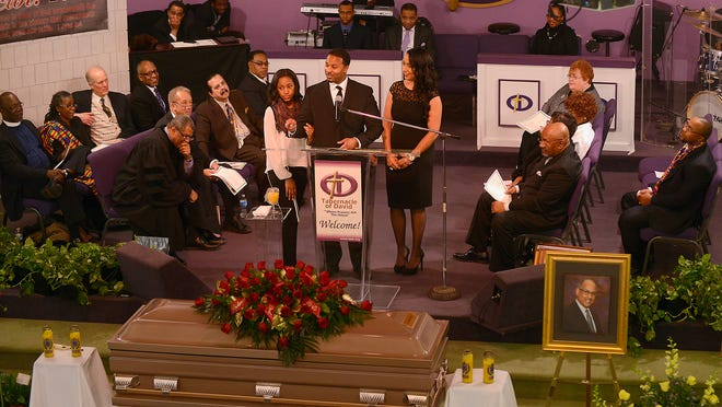 Brandon Clark, the Rev. Dr. Michael Murphy's son, speaks at his father's funeral Wednesday, flanked by the Rev. Murphy's daughter, Rachel (right), and granddaughter Danielle Embry-Clark (left).