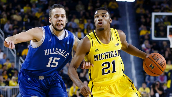 Michigan Wolverines guard/forward Zak Irvin (21) dribbles the ball as Hillsdale Chargers forward Rhett Smith (15) defends in the first half at Crisler Center, Nov. 15, 2014.