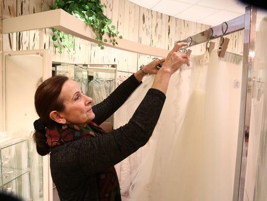 Co-owner, Kathy Belmont sorts veils inside the showroom