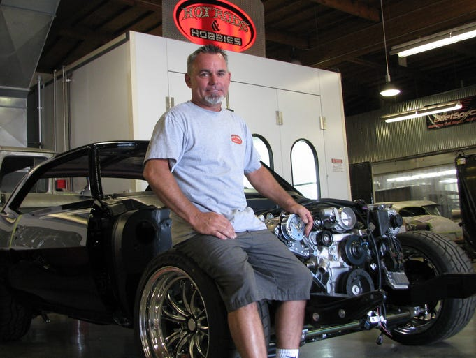 Scott Bonowski, owner of Hot Rods and Hobbies in Signal Hill, Calif., sits on the tire of a muscle car under restoration