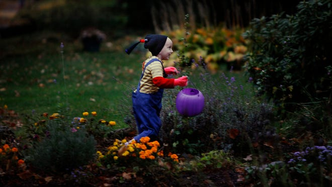 Amanda Conrow walks up to a neighbors house on Garson Ave to trick or treat on Halloween night. At five years old, Amanda has been battling brain cancer for two years. She was dressed as Agnes, a character from her favorite movie Despicable Me.