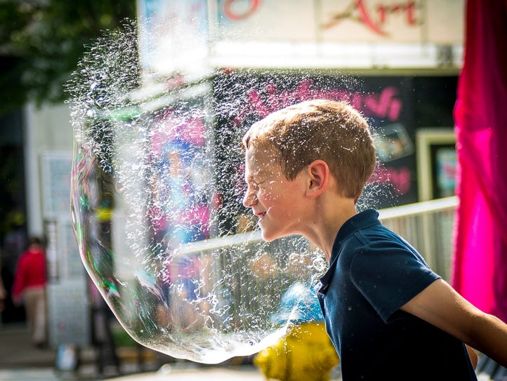 Matthew Evola pops a giant bubble with his face in