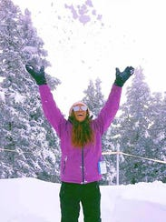 Gracie Dozier tosses some snow after the storm.