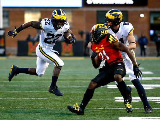 Michigan running back Karan Higdon, left, rushes past