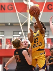Walnut Hills' Sean Kelly Darks drives to the basket as McAuley's Lexi Fleming takes a charge Saturday, March 3rd at Princeton High School
