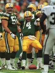 Brett Favre is hoisted by teammates Frank Winters (52) and Earl Dotson after Oakland's K.D.Williams was penalized for unnecessary roughness during the first quarter.