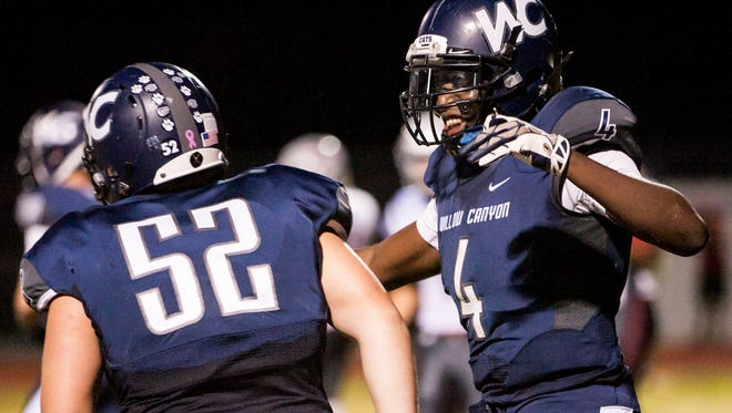 Willow Canyon running back Marcus Singleton (4) and offensive lineman Travis Gutshall (52) celebrate in the end zone after Singleton scored a touchdown in the second quarter against Ironwood on Friday, Oct. 3, 2014, in Surprise, Ariz.