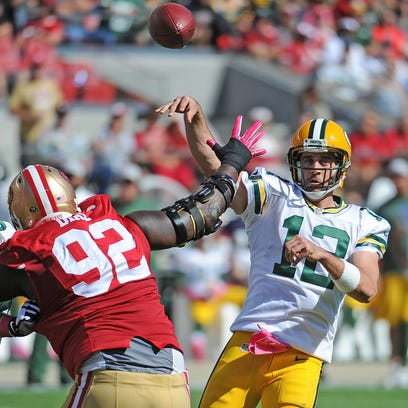 Packers quarterback Aaron Rodgers (12) throws under