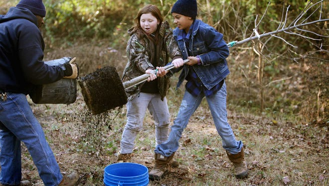 Marissa Horn and Aaryon West remove a tree from a plastic bucket at a previous Arbor Day planting in Lafayette Park.