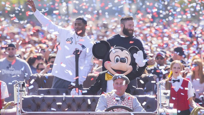 New England Patriots players Julian Edelman (right) and Malcolm Butler were joined by Mickey Mouse as they celebrated their team's Super Bowl XLIX championship victory with a special cavalcade down Main Street, U.S.A. at Disneyalnd park in Anaheim, California,, on Monday.