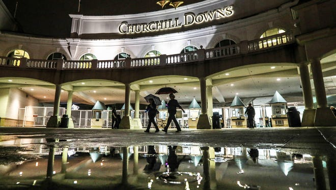 11: 45 p.m. As the rain picks up, staff and patrons make their way out of Churchill Downs after opening night. April 30, 2016