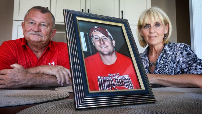Karl and Brenda Cooley at their home with a photo of their son, Adam, who deals with heroin addiction.May 13, 2016