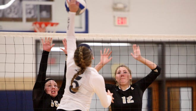 Buffalo Gap's Camille Ashby, left, and Emily Hanger jump to block a spike from R.E. Lee's Meghan Wood during the 2A girls volleyball championship at R.E. Lee High School in Staunton on Saturday, Nov. 12, 2016.