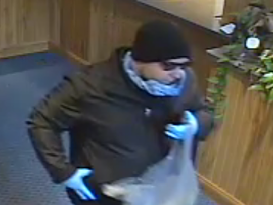 A male suspect is shown robbing the Bank of Millbrook's