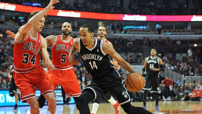 Brooklyn Nets point guard Shaun Livingston (14) is defended by Chicago Bulls small forward Mike Dunleavy (34) during the first quarter at the United Center.