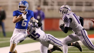 Dixie's Jaden Harrison runs with the ball past Tooele's Blake Paystrup and Lincoln Powers during the 3AA semifinal football game at Rice-Eccles Stadium in Salt Lake City on Friday. Dixie won 45-6.