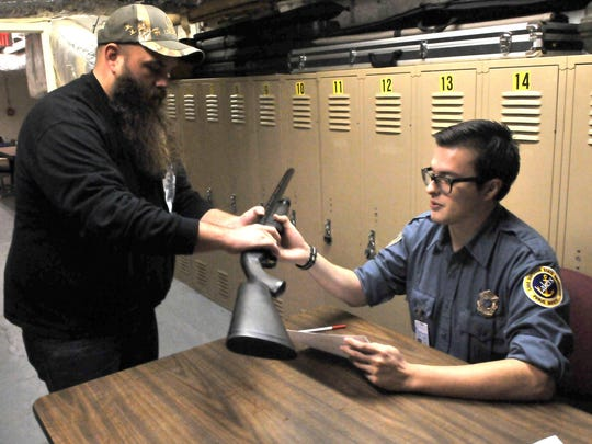 Logan Archibald, left, hands over a 12-gauge shotgun to Public Safety Officer Angel Gama-Diaz at Lake Superior State University's administration building. LSSU forbids carrying concealed weapons on campus.