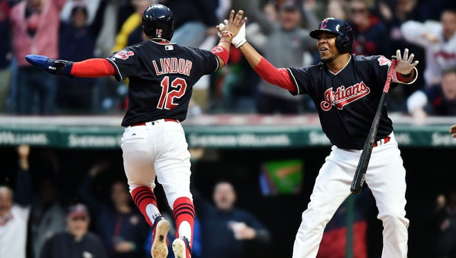 Francisco Lindor celebrates with teammate Edwin Encarnacion after scoring the winning run in the 10th inning against the Chicago White Sox.