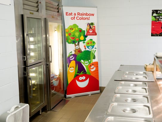 A sign with vegetables stands in the lunch line at