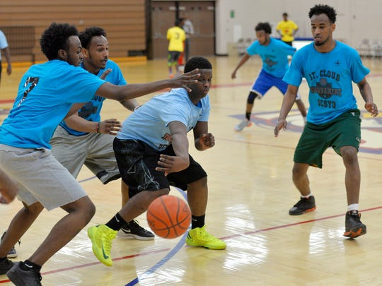 A player from the Hall of Fames, center, tries to pass the ball around three defenders from the Originals Saturday during the St. Cloud Somali Youth Organization Basketball Tournament at Apollo High School. Six teams faced off during the 5 on 5 tournament.