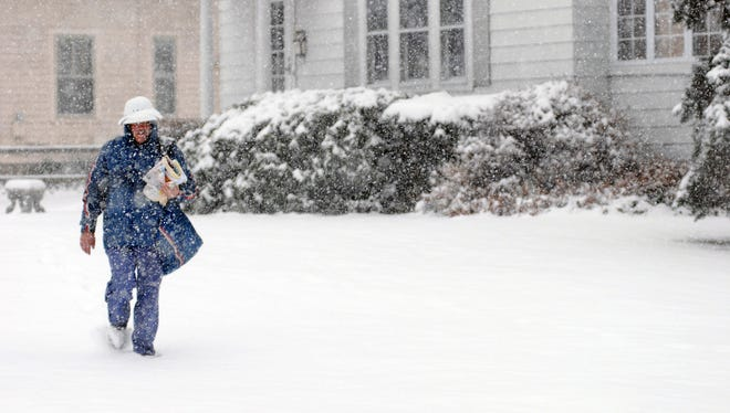 USPS postal carrier Doug Fischer delivers mail in the village of Hyde Park.