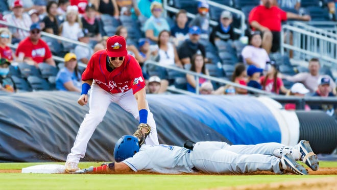 Amarillo Sod Squad third baseman David Marcano (left) tags out the Tulsa Drillers Alec Sanchez as he unsuccessfully tried to stretch a double into a triple Wednesday night in a Texas Collegiate League Northern Division playoff series at Hodgetown.