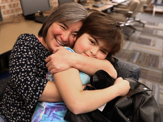 Jesse Pennington-Cross is embraced by her mom, Carla.