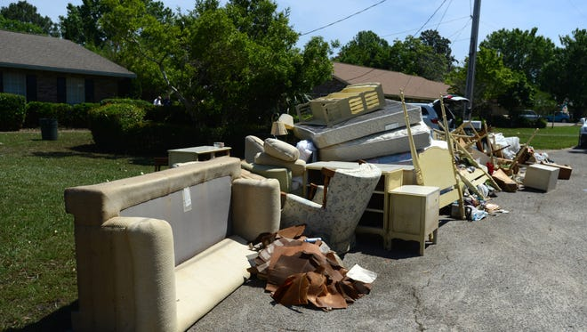 Flood debris lines Dracena Way in Gulf Breeze as home owners and volunteers begin the damage removal and clean up process.